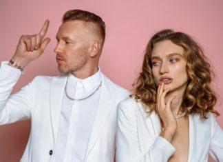 Mężczyzna w białym garniturze i kobieta w futrze na różowym tle