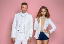Mężczyzna w białym garniturze i dziewczyna w białej marynarce i czarnych spodniach na różowym tle