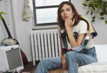 Dziewczyna w jeansach siedząca na łóżku