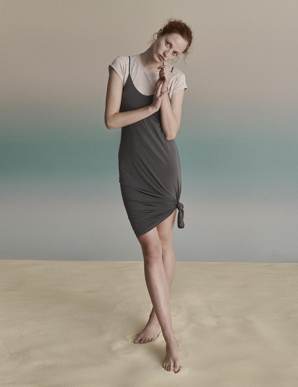Mloda ruda dziewczyna stoi na teczowym tle ubrana w siwa sukienke i bezowy tshirt