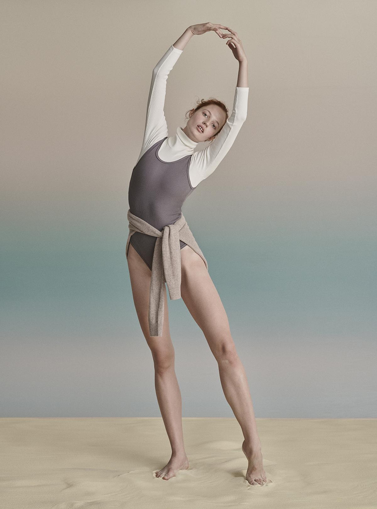 mloda ruda dziewczyna ubrana w szare body na biale body w pozie baletnicy na teczowym tle