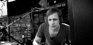 Czarno-białe zdjęcie mężczyzny za konsoletą