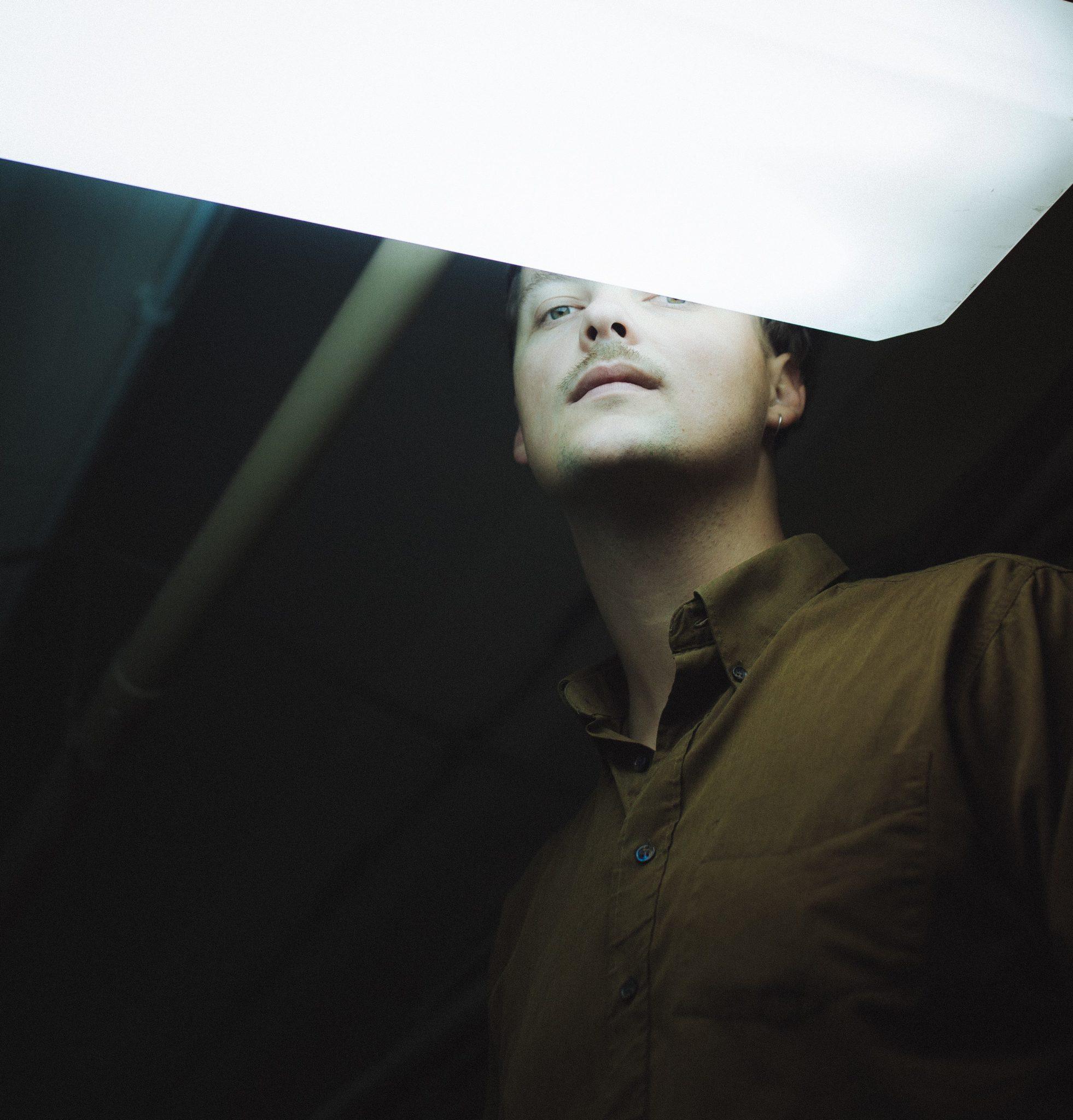 Na zdjeciu widzimy mlodego mezyczyzne sfotografowanego od dolu polowe twarzy przykrywa lampa