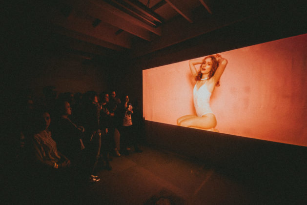 Teledysk wyświetlany w projektora i tłum ludzi