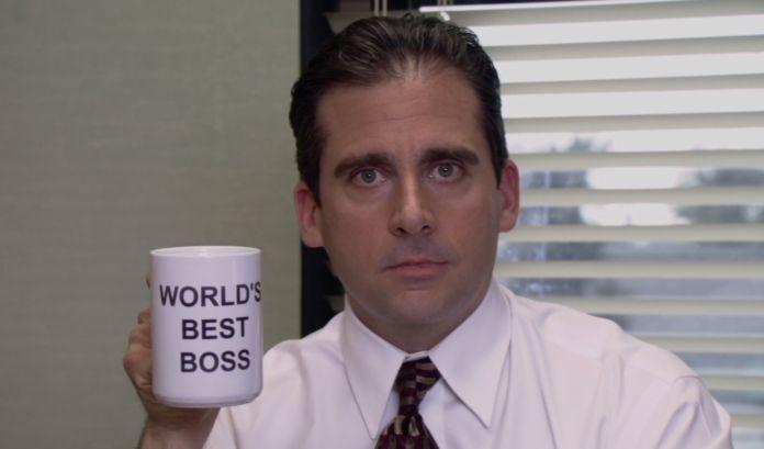 Mężczyzna w koszuli z kratem i kubkiem World's best boss