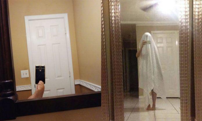 Stopa trzymająca telefon i osoba przebrana za ducha