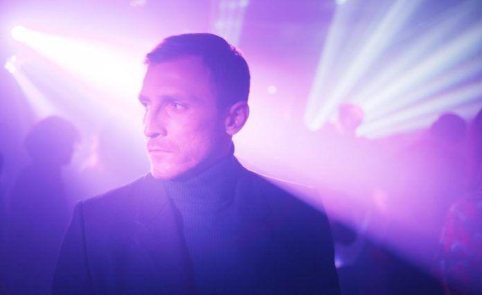 Mężczyzna ubrany w ciemny golf w klubie