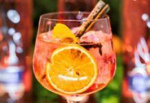 Czerwony drink z pomarańczą i laska cynamonu