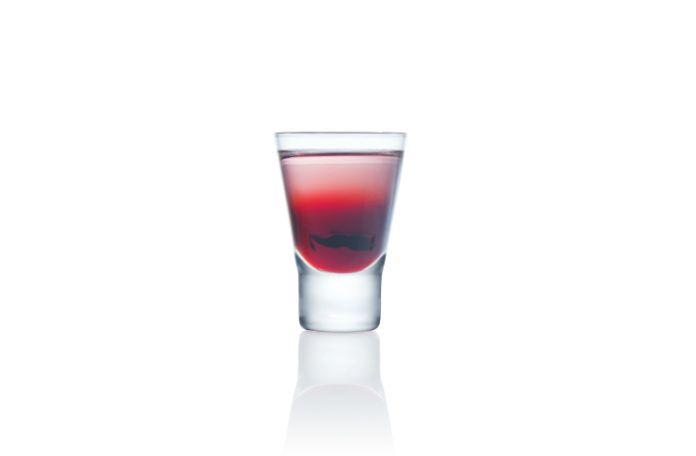 Czerwony drink w kieliszku od wódki
