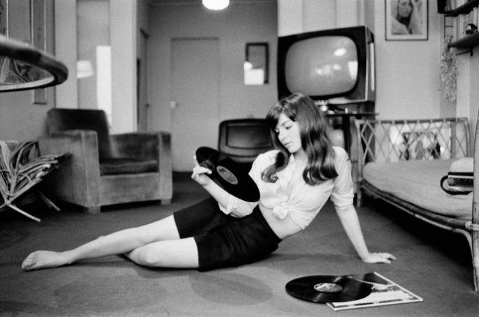 Dziewczyna siedząca na podłodze z winylem w ręku