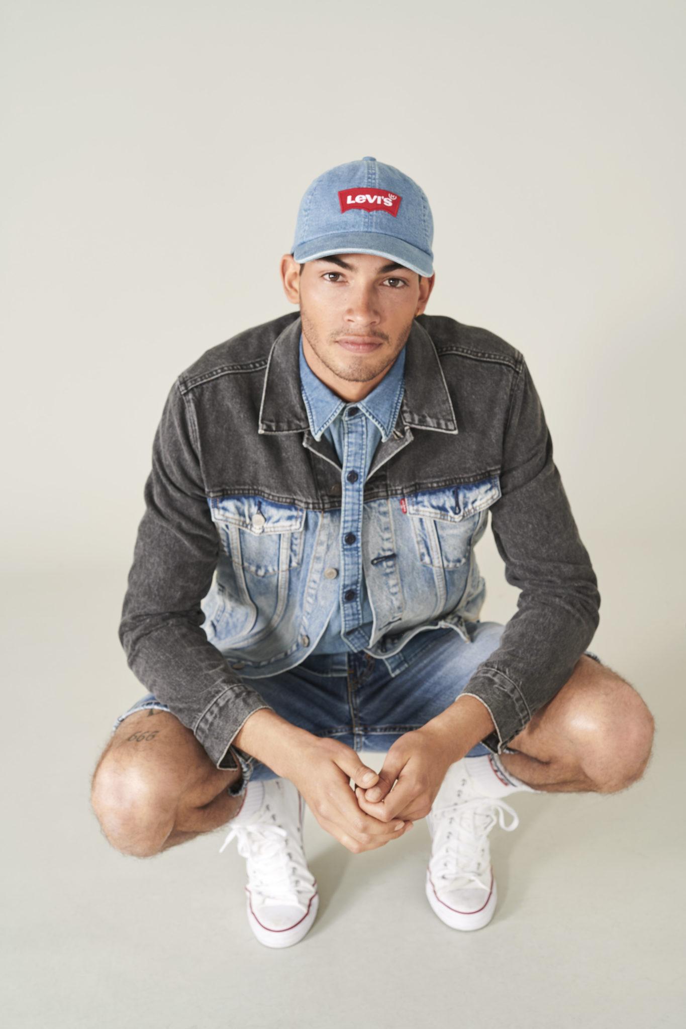 Chłopak ubrany w jeansową kurtkę i czapkę z napisem Levi's