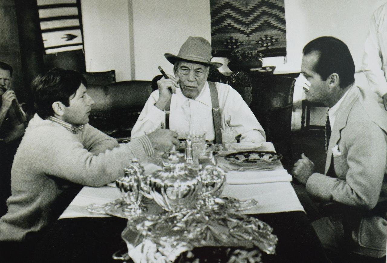 Czarnobiale zdjecie trzech mezczyzn siedzi przy stole i bawia sie