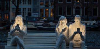 Rzeźba przedstawiająca trójkę ludzi ze smartfonami