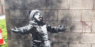 Mural Banksy'ego przedstawiający dziecko łapiące śnieg na język