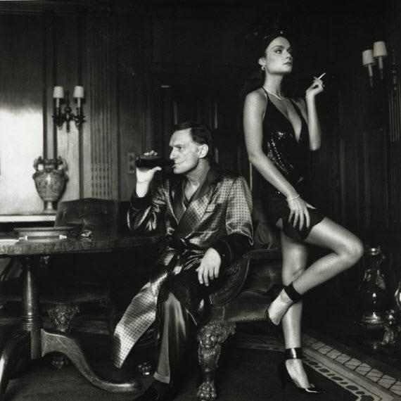 Mężczyzna w szlafroku z butelką wina i kobieta z papierosem obok