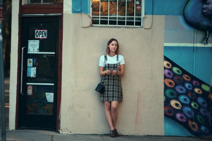 Dziewczyna w sukience w kartę stojąca pod ścianą