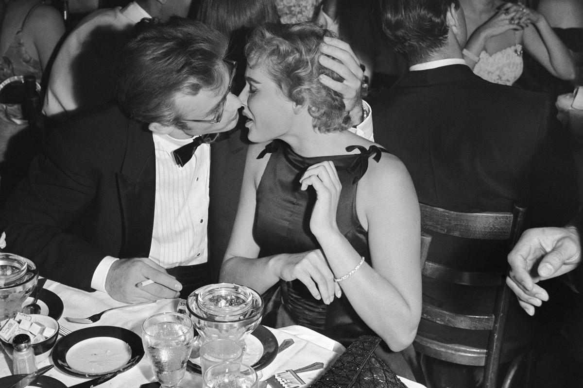 Dwojga mlodych ludzi siedzacych przy stole w akcie pocalunku czarno biale zdjecie