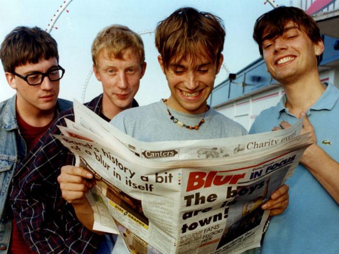 Czterech chłopaków czytających gazetę
