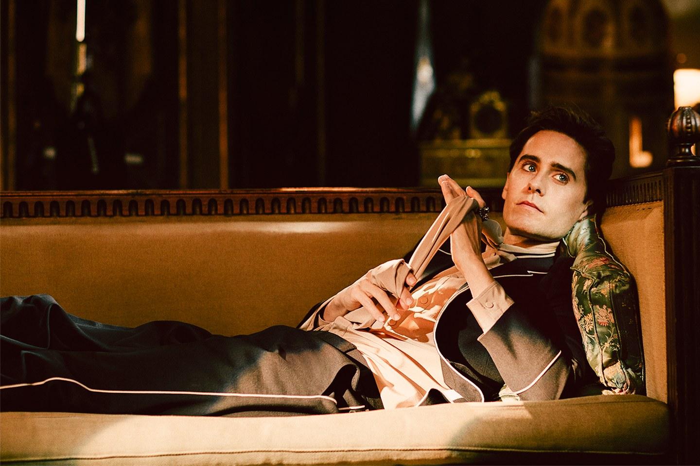 Mlody mezczyzna lezy na bogatej skorzanej kanapie ubrany w eleganki garnitur