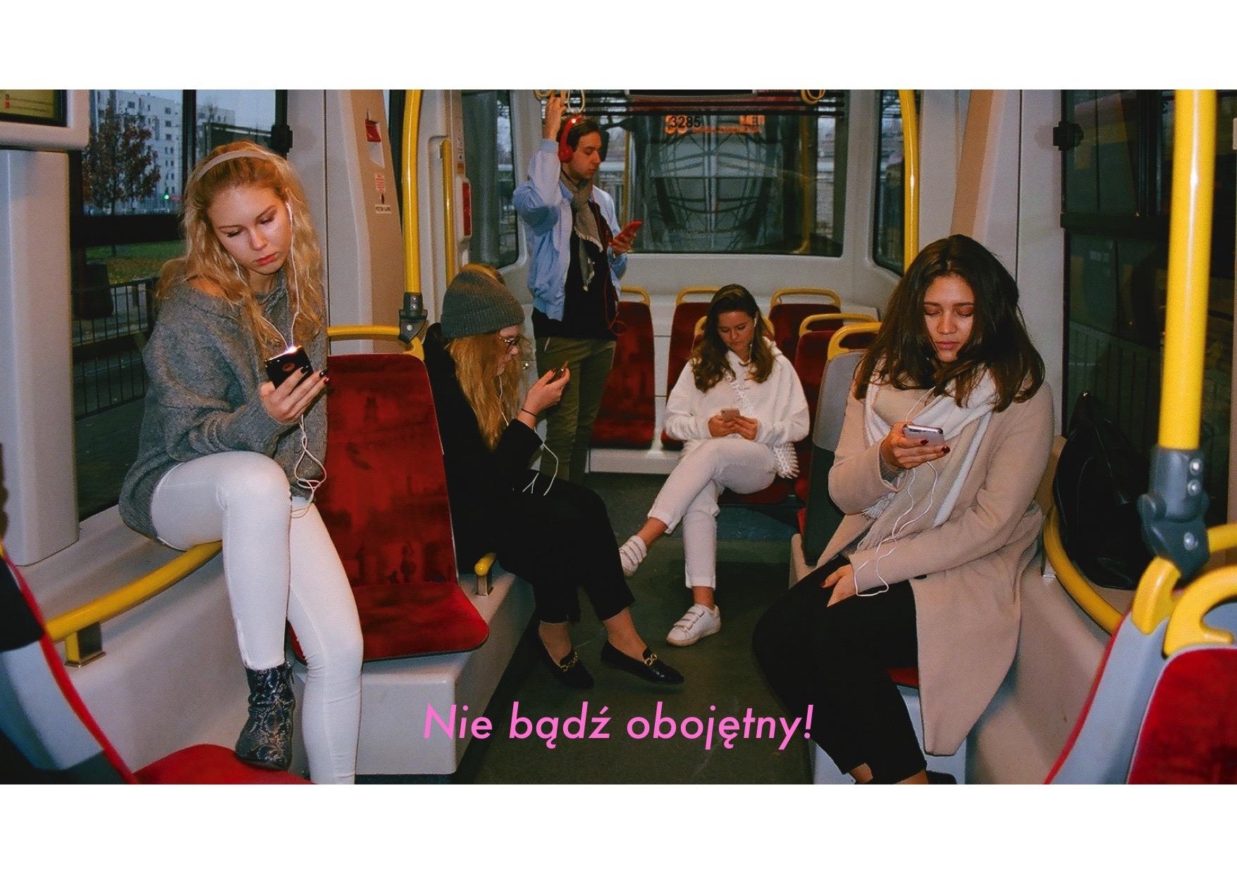 Kilka osób w tramwaju, każda patrzy w telefon