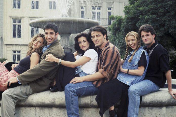 Grupa przyjaciół siedząca na fontannie