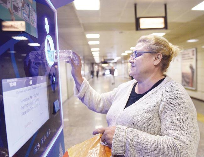 Kobieta wrzucająca butelkę do automatu