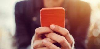 Ręce trzymające smartfon w czerwonej obudowie