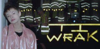 Dziewczyna w różowej kurtce i krótkich włosach na tle napisu WRAK