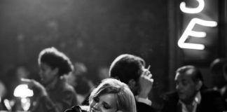 Czarno-białe zdjęcie dziewczyny siedzącej przy barze