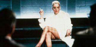 Blondynka ubrana w białą sukienkę i biały płaszcz pali papierosa i siedzi ze skrzyżowanymi nogami