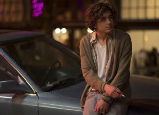 Chłopak stojący z papierosem przy samochodzie