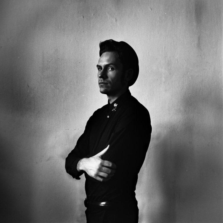 Mężczyzna w czarnej koszuli na tle jednolitej ściany
