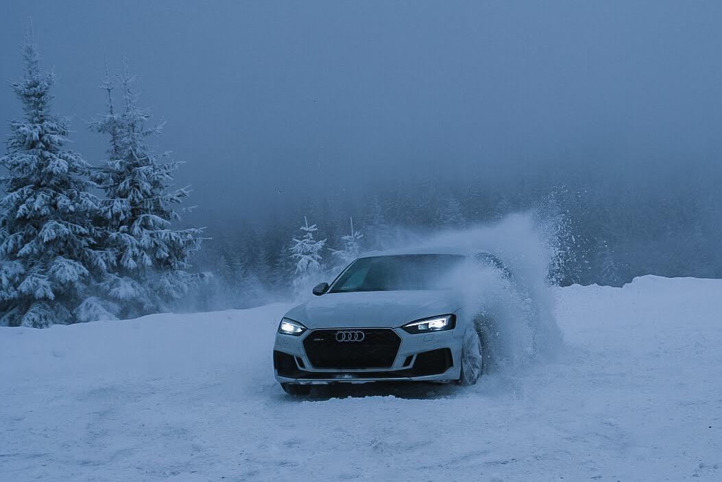 Biały samochód driftujący przez śnieg