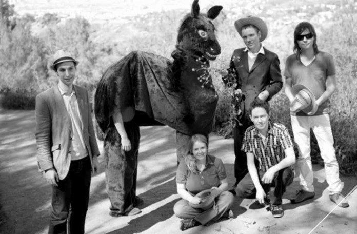 Czarno-białe zdjęcie grupy ludzi stojących z koniem