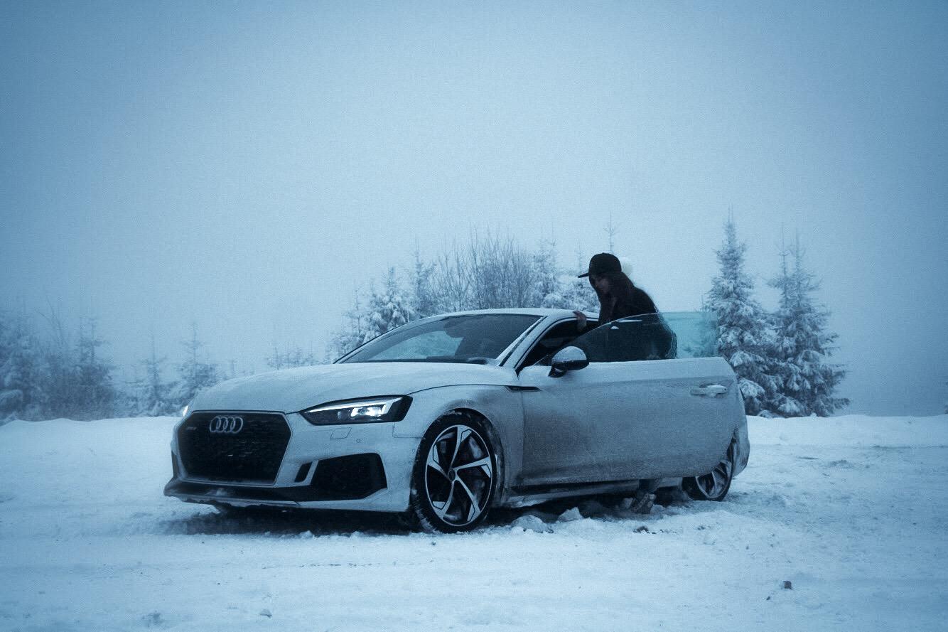 Dziewczyna wsiadająca do białego samochodu na polanie pełnej śniegu