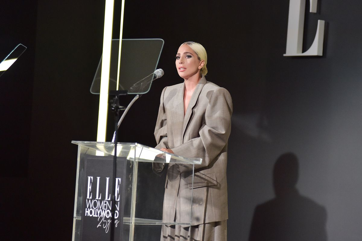 Mloda kobieta w upietych blond wlosach daje przemowienie ubrana w meski za duzy garnitur na ciemnej scianie