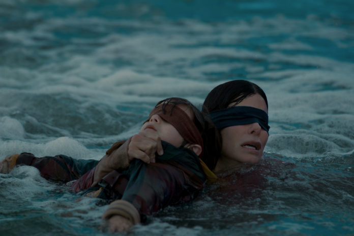 Kobieta z zasłoniętymi oczami w morzu z dzieckiem