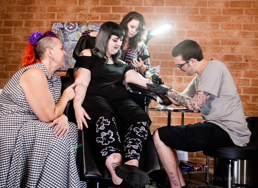 Mężczyzna tatuuje coś na ręku kobietu