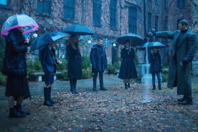 Kilka osób z parasolami i jedna osoba wysypująca prochy z urny