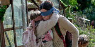 Kobieta z zawiązanymi oczami trzymająca na rękach dziecko