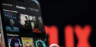 Ręka trzymająca telefon z aplikcją Netflix