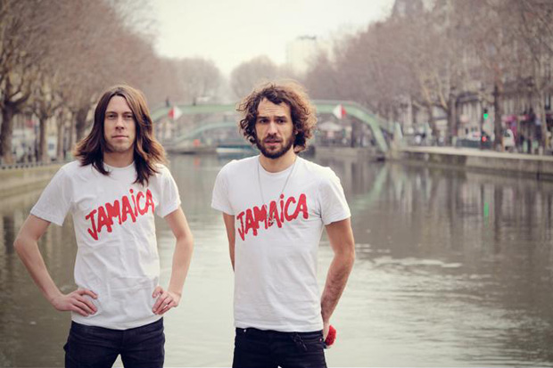 Dwoch mezczyzn w bialych tshirtach z napisem JAMAICA stoja na tle rzeki