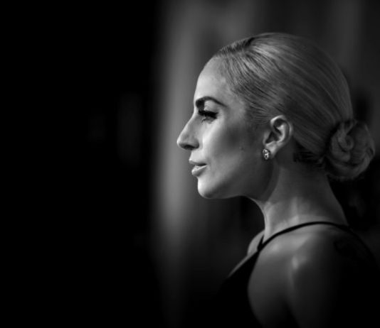 Czarno biale zdjecie profilu blondynki ubranej w ciemna suknie wieczorowa