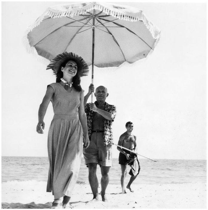 Kobieta spacerująca po plazy, za nia mezczyzna z parasolem