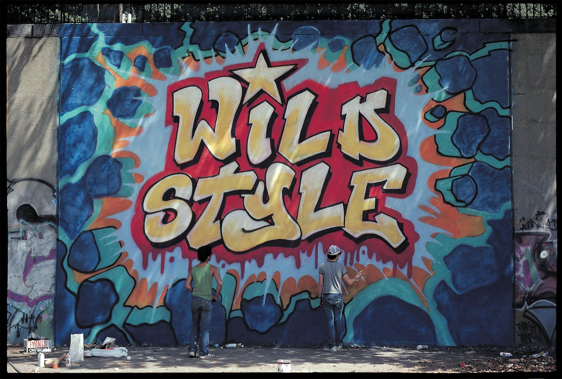 Na zdjeciu widzimy sciane pokryta kolorowym grafitti najbardziej rzuca sie w oczy napis wild style
