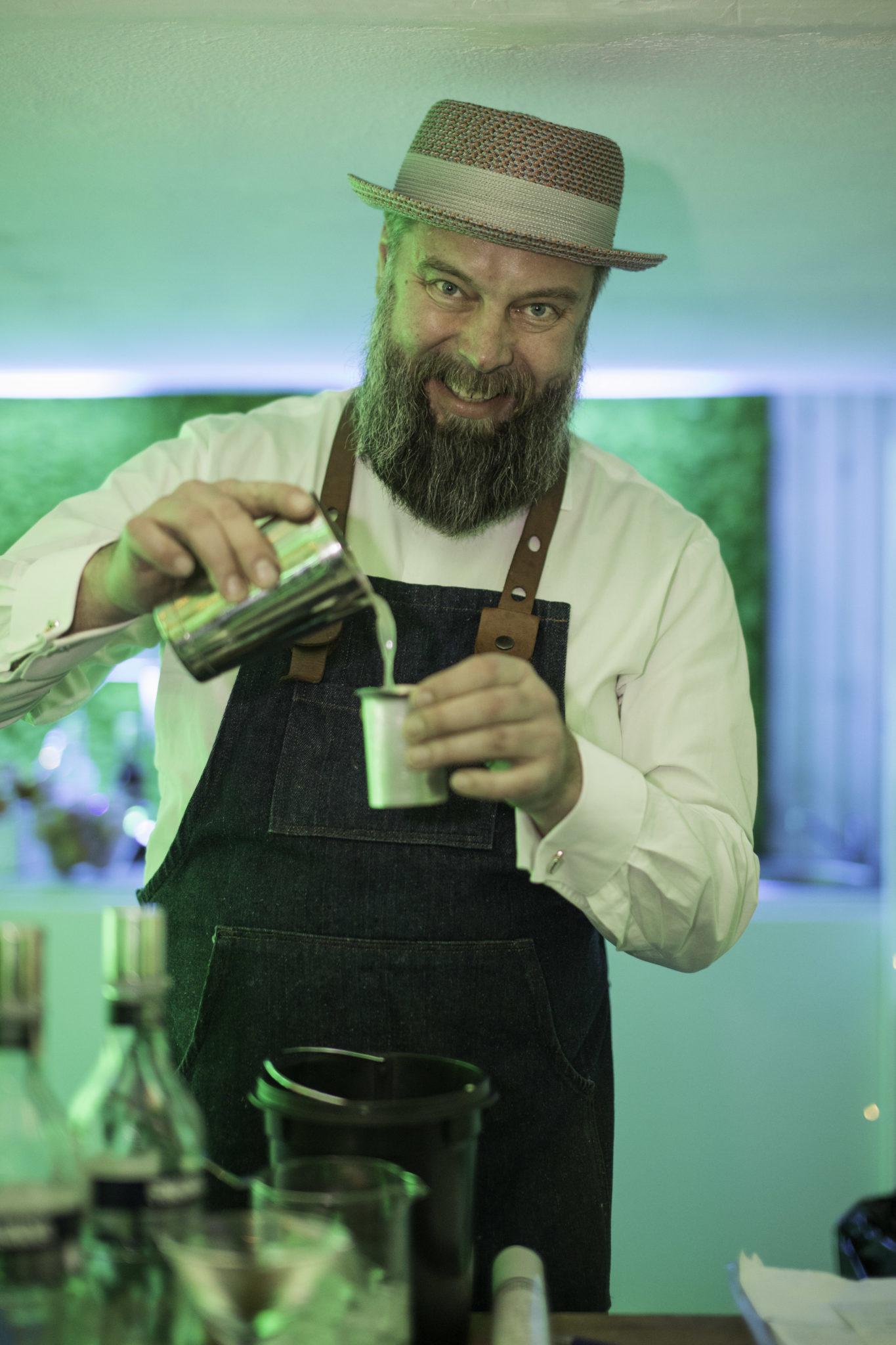 Mężczyzna z brodą robiący drinka