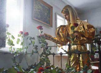 Dziewczyna w złotym kombinezonie przy łóżku na którym leżą róże