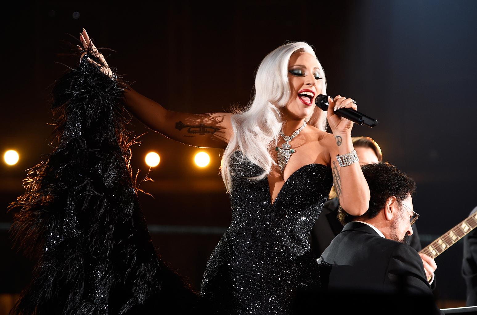 Na zdjeciu widzimy spiewajaca kobiete blondynke ubrana w piekna czarna suknie wieczorowa
