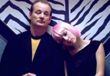 Kobieta w różowej peruce opierająca głowę na ramieniu mężczyzny