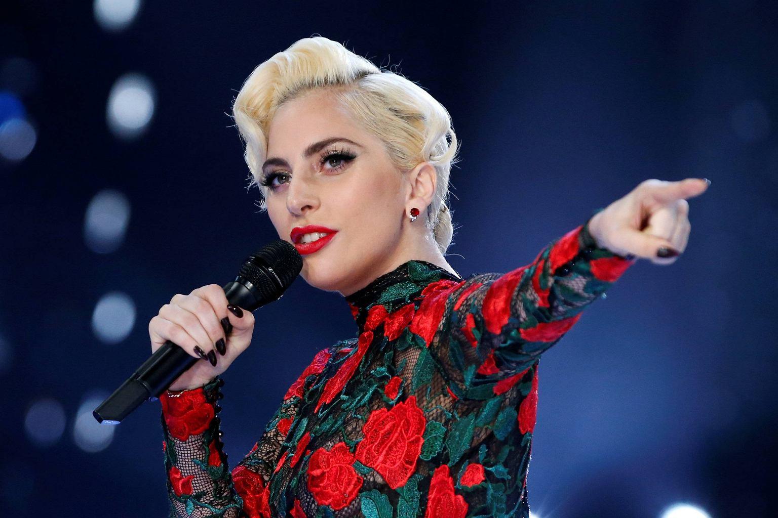 Na niebieskim tle spiewa kobieta w blond wlosach w czerwonej sukience